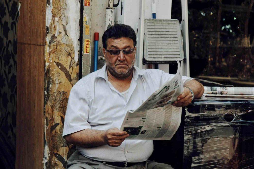 ilustrasi orang tua membaca koran